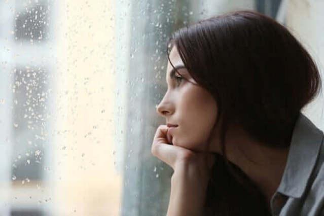 Frau mit Trauma schaut aus dem Fenster