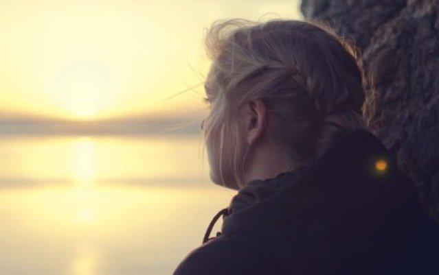 Frau sieht Sonnenaufgang