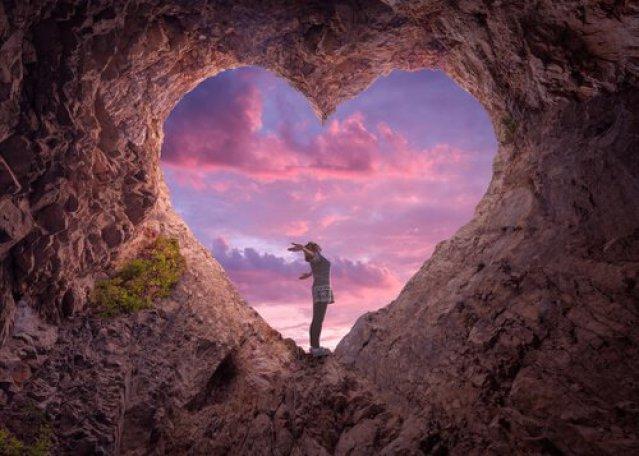 Frau steht in einem Herz aus Stein