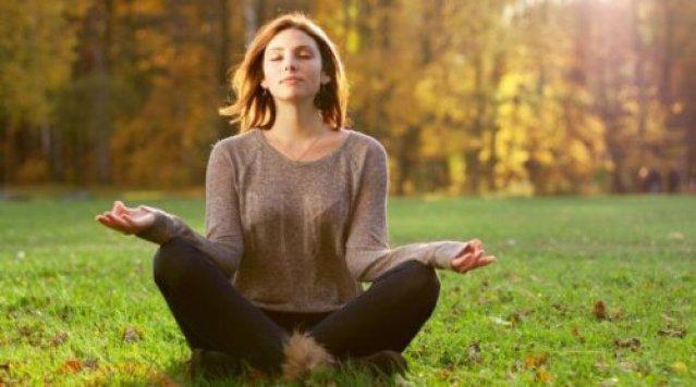 Meditierende Frau auf einer Wiese