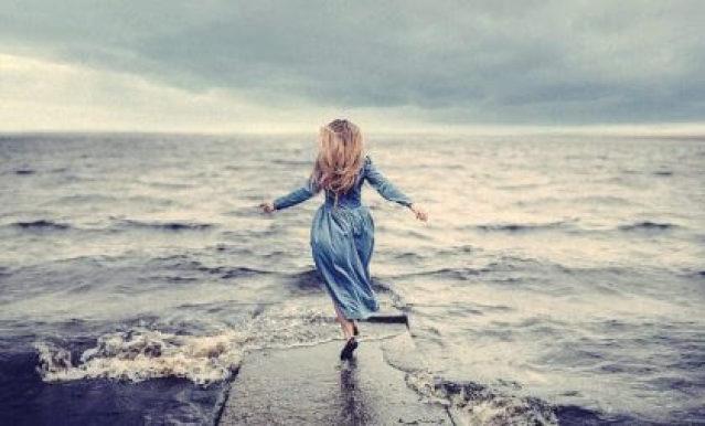 Frau auf einem steg im Meer
