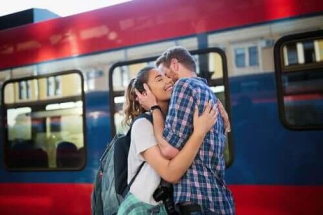 Junges Paar umarmt sich vor Zug