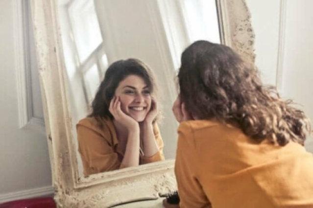 Frau lächelt in den Spiegel