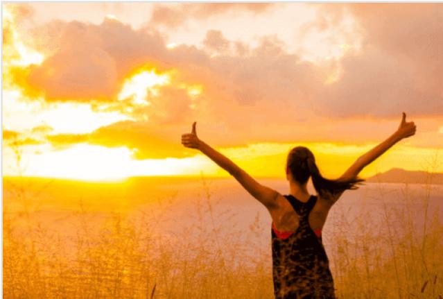 Glückliche Frau beim Sonnenaufgang